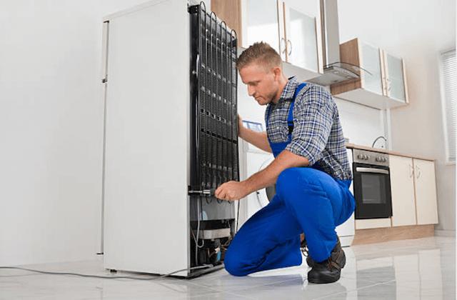 appliance repairman behind refrigerator